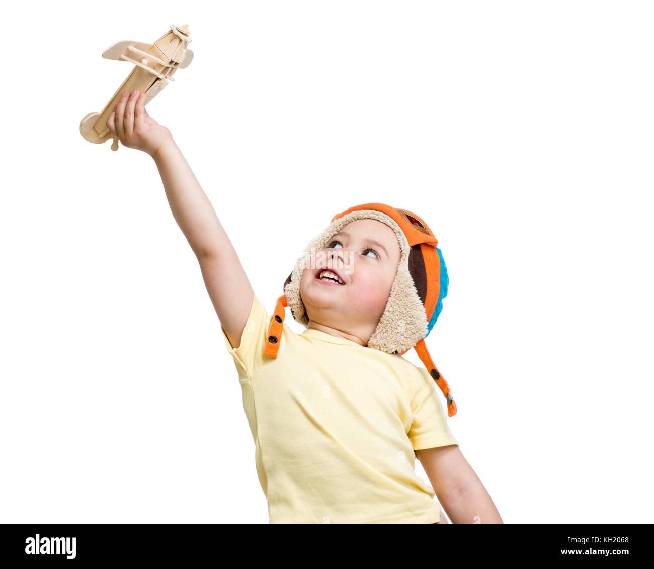 Glückliches Kind Junge in Helm Pilot spielt mit Holzspielzeug Flugzeug. auf weißem Hintergrund. Stockbild