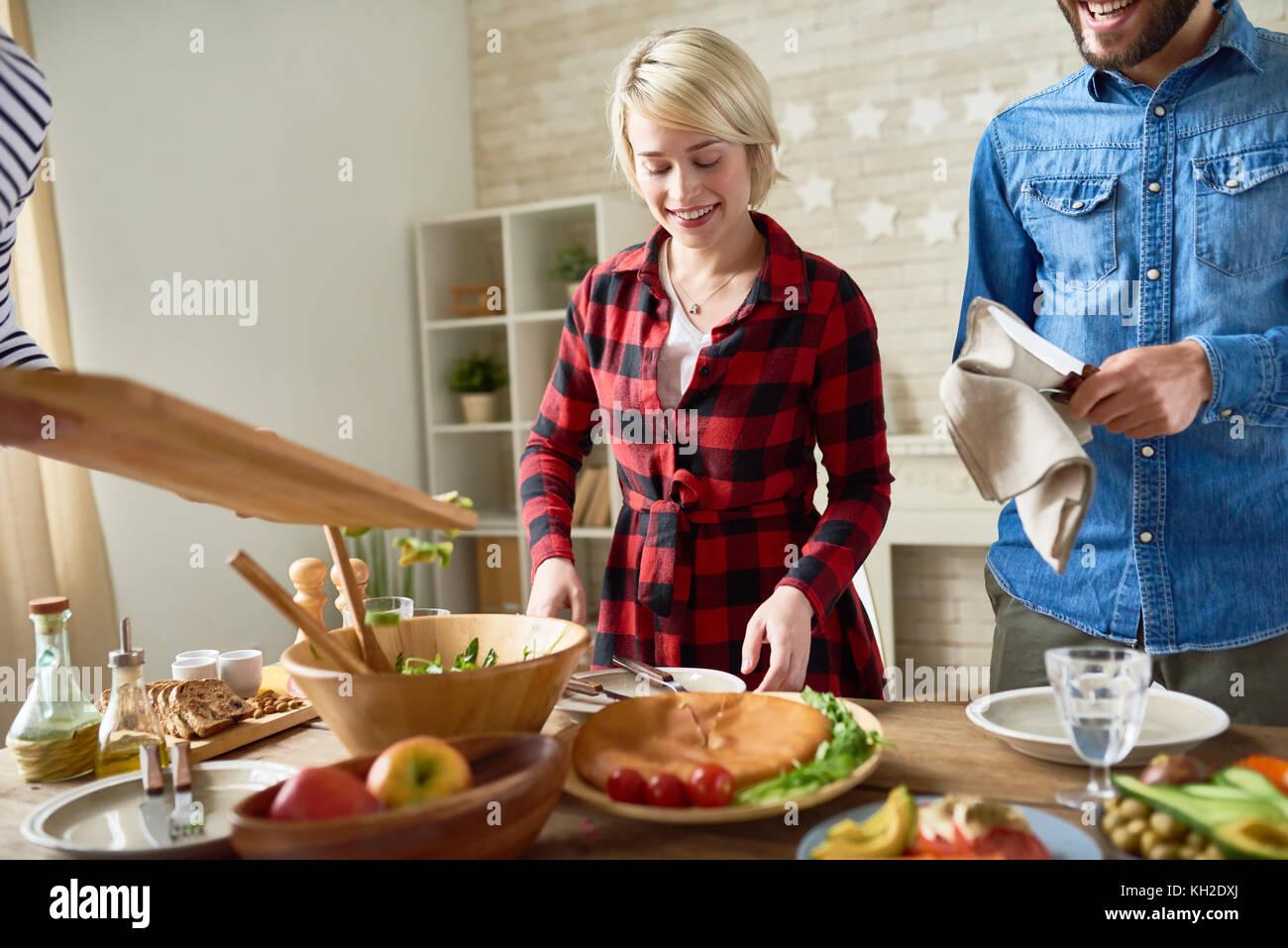 Portrait des modernen junges Paar stehend an festlichen Tisch essen vorbereiten und lächelnd, Fokus auf Happy Stockbild