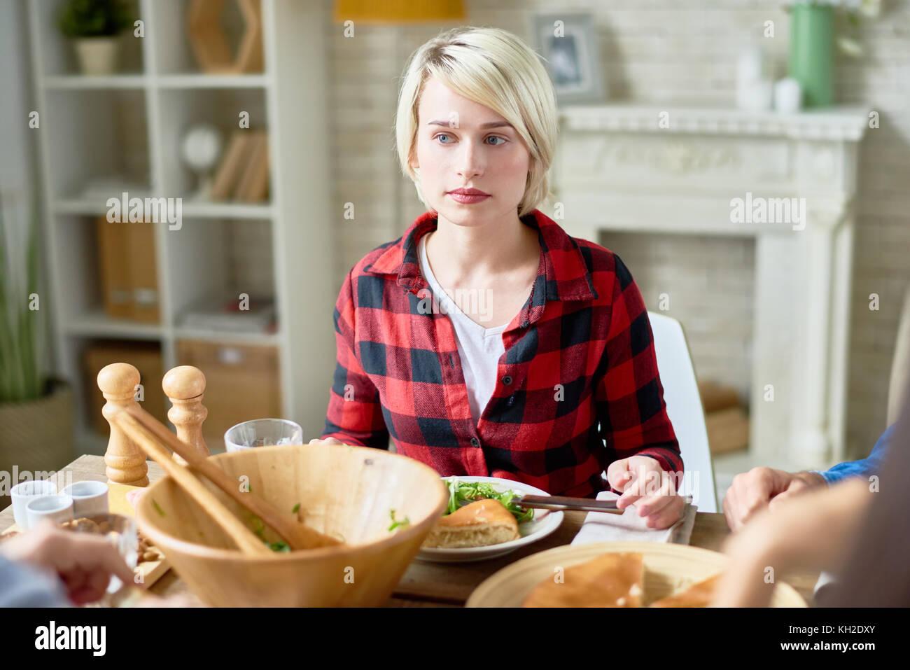 Porträt der blonde junge Frau am festlich gedeckten Tisch sitzen mit Freunden feiern Danksagung Stockbild