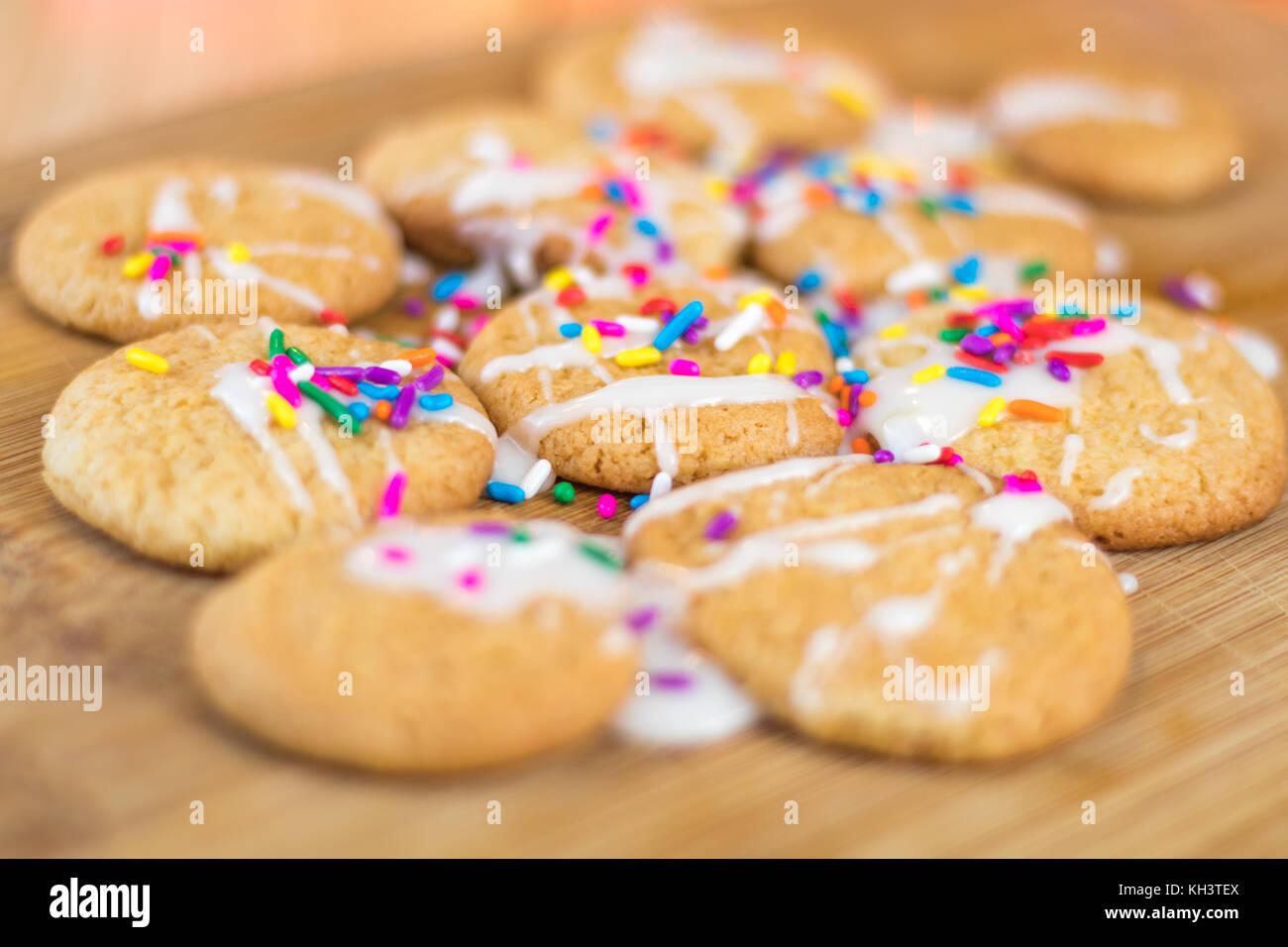 Frisch gebackene Sugar Cookies mit weißer Zuckerglasur und Rainbow farbige Streusel auf Holzbrett, selektiver Stockbild