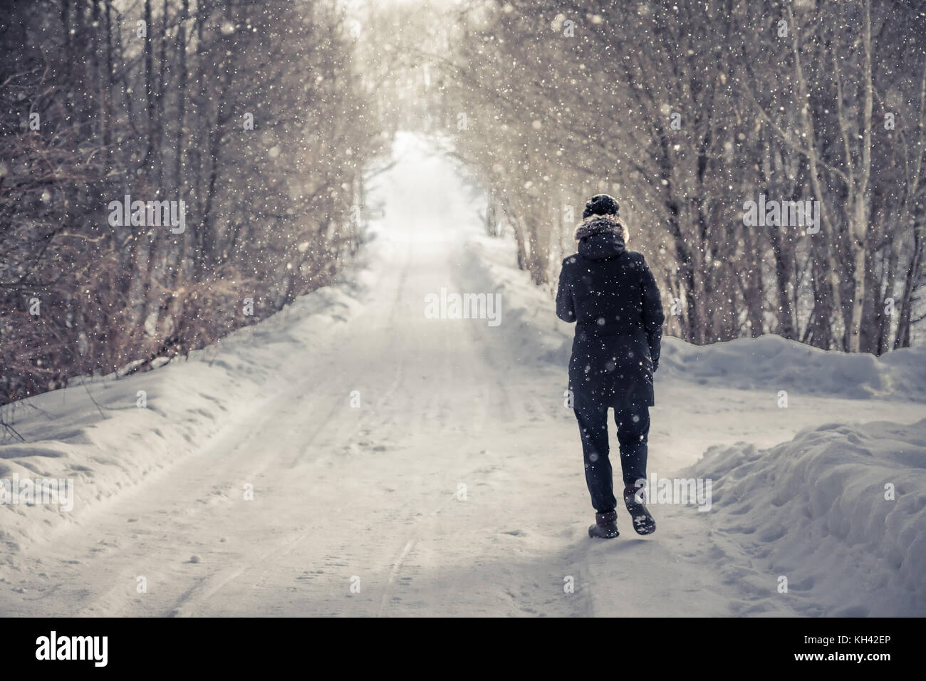 Einsame Frau zu Fuß auf verschneite Straße zwischen Bäumen Gasse mit Licht am Ende des Weges in kalten Wintertag Stockfoto