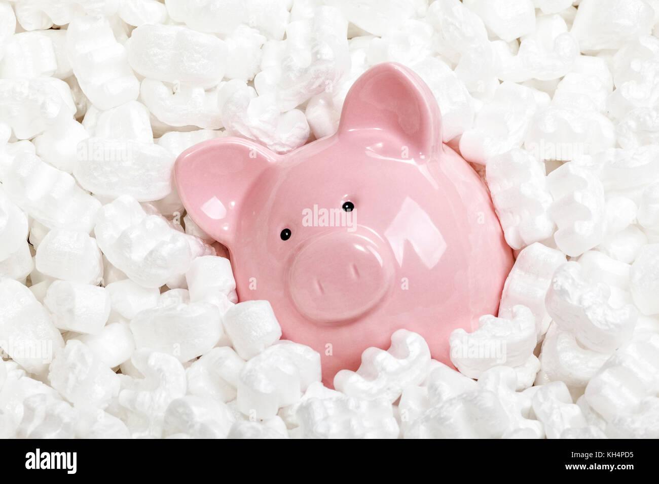 Sparschwein und Polystyrol Erdnüsse Hintergrund Stockbild