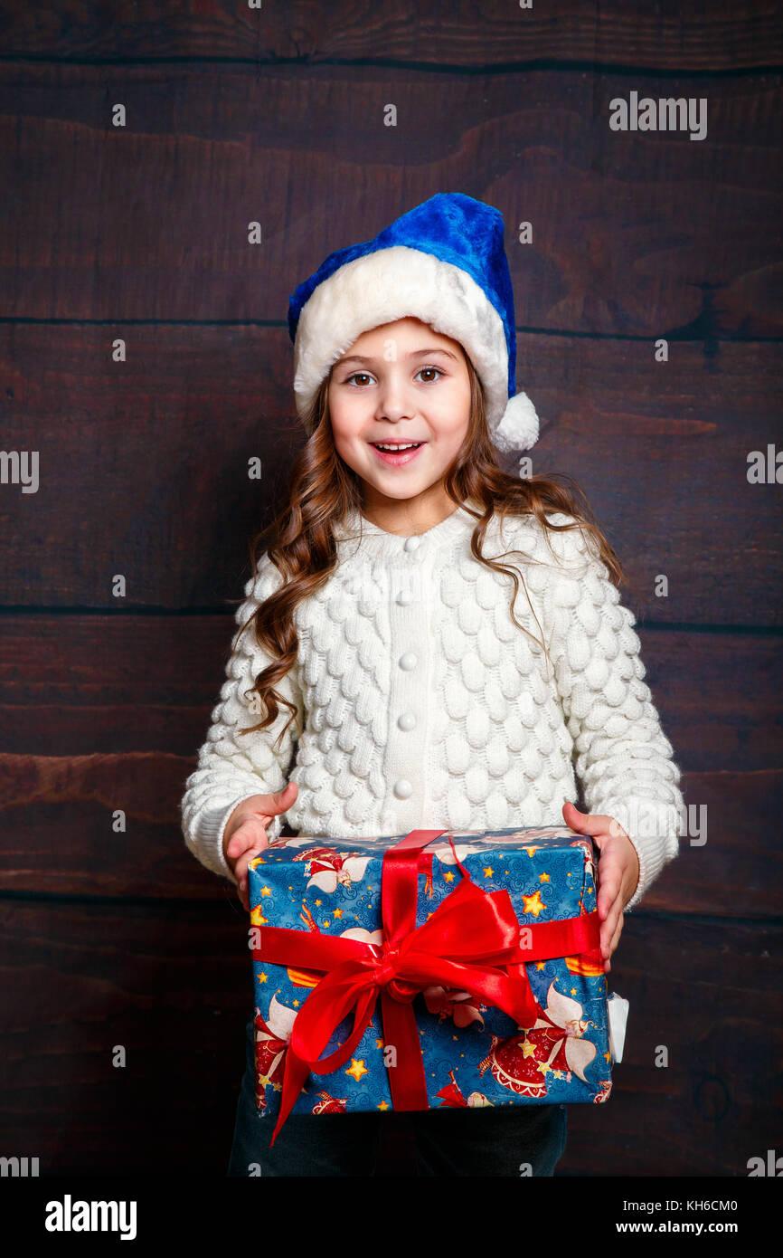 Glückliche kleine lächelnde Mädchen mit Weihnachtsgeschenk ...