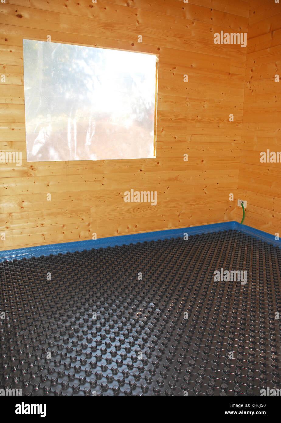 Ein Zimmer in einem teilweise konstruierten Holzhaus mit schwarzem Kunststoff isolierte Panel in geschäumtem Stockbild