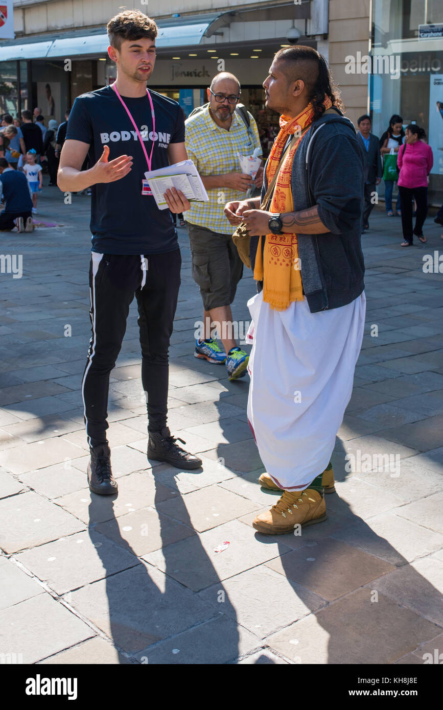 Ein Fitnessstudio Ausbilder und Mitglied der Hare Krishna Chatten in Newcastle City Centre. Stockbild