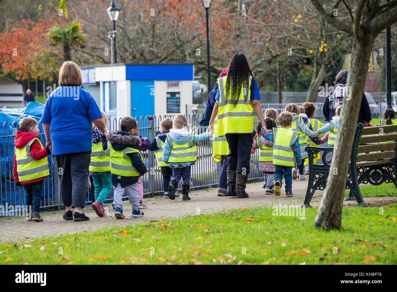 Eine Gruppe von Kindern im Vorschulalter zu Fuß mit ihren Lehrern und Lehrassistenten auf eine Reise heraus. Stockbild