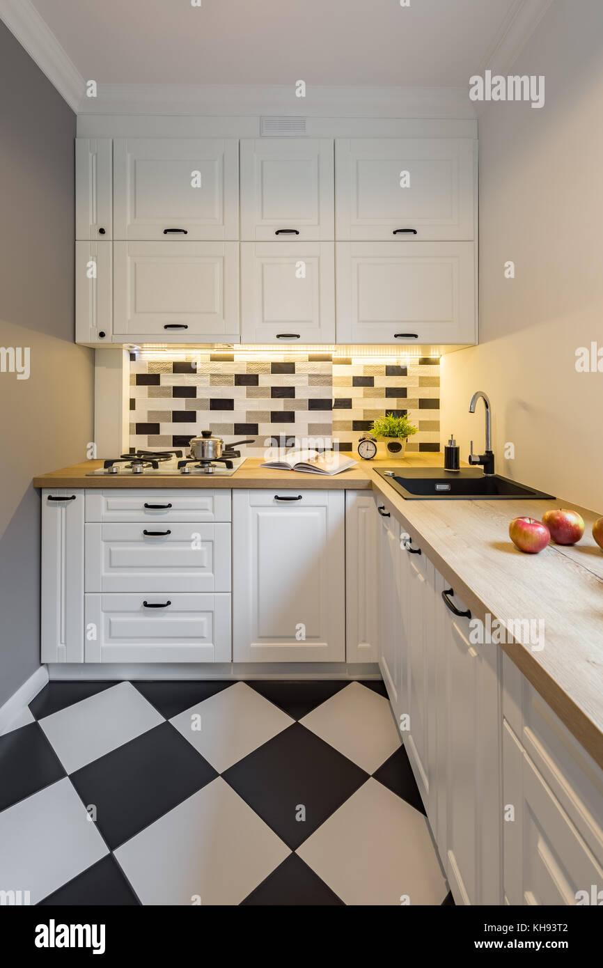 Kleine Küche mit modernen schwarzen und weißen Bodenfliesen ...