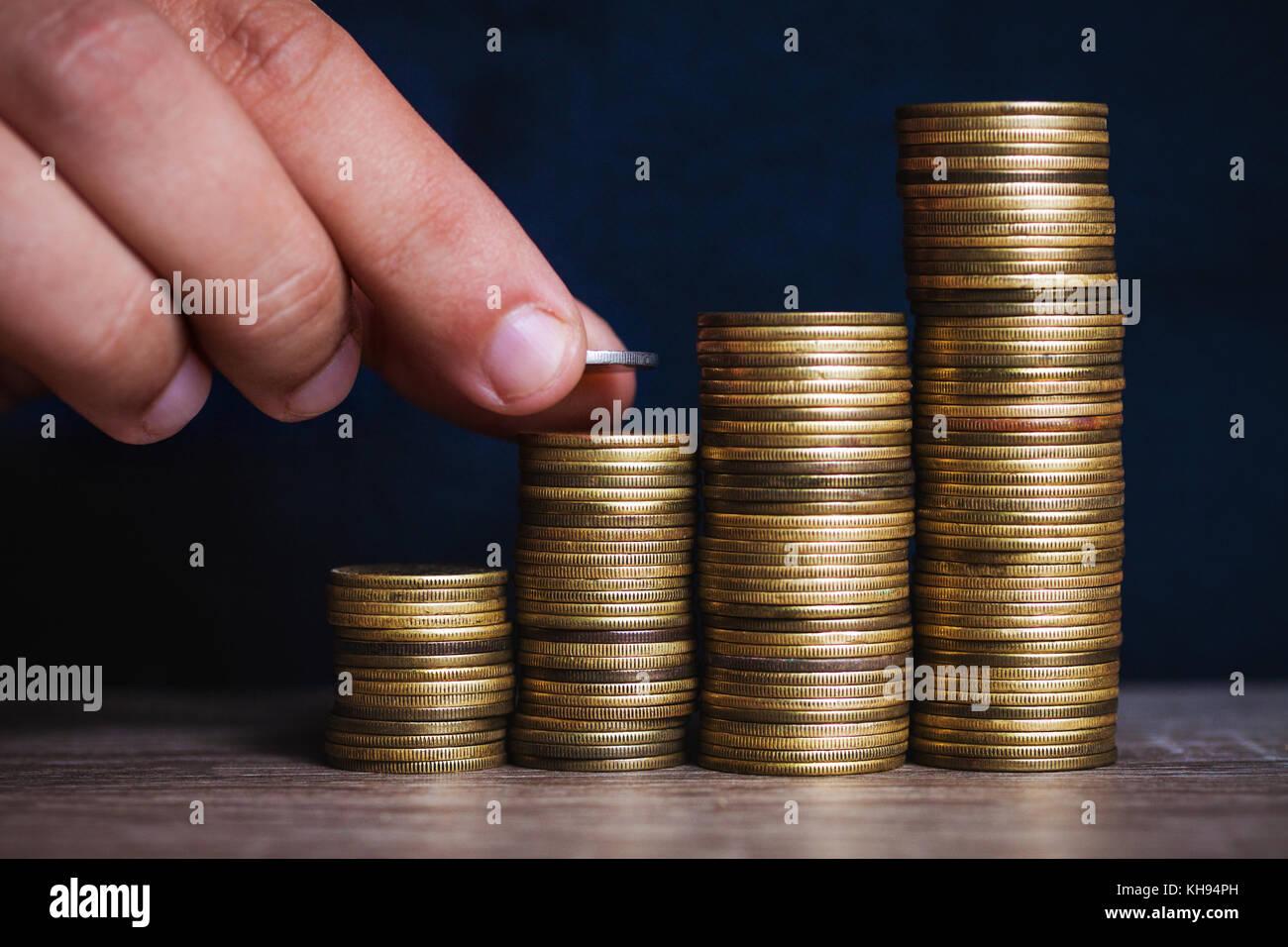 Die Hand des Menschen legen Geld Münzen Münzen zu stapeln. Geld, finanziellen, geschäftlichen Wachstum Stockbild