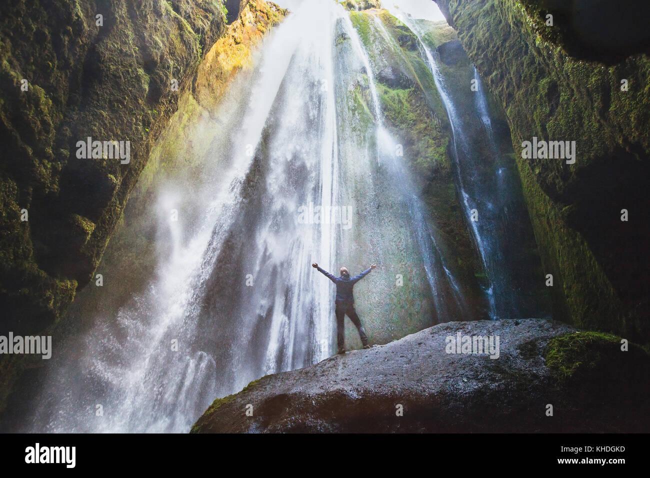 Reisen nach Island, Person mit erhobenen Händen stehen in Wasserfall Gljufrabui, inspirierte Happy Traveler Stockbild