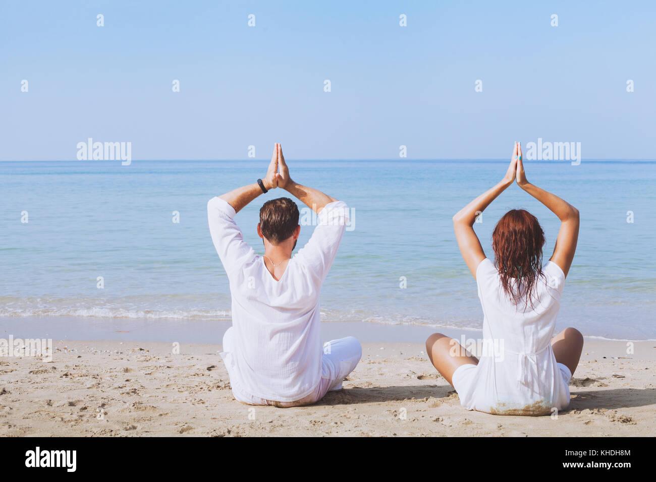 Yoga am Strand, zwei Menschen in weißen Kleidern üben Meditation, gesunden Lebensstil Hintergrund Stockbild