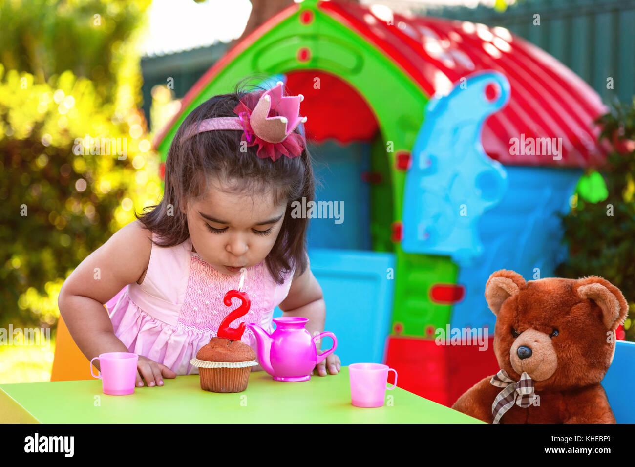 Baby Kleinkind Mädchen im Freien zweiten Geburtstag party blowing Kerze auf Muffin. Teddy Bär als bester Stockbild