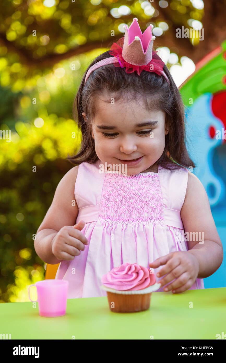 Baby Kleinkind Mädchen in der Party im Freien im Garten, glücklich und lächelnd an Cupcake mit süßen Stockbild
