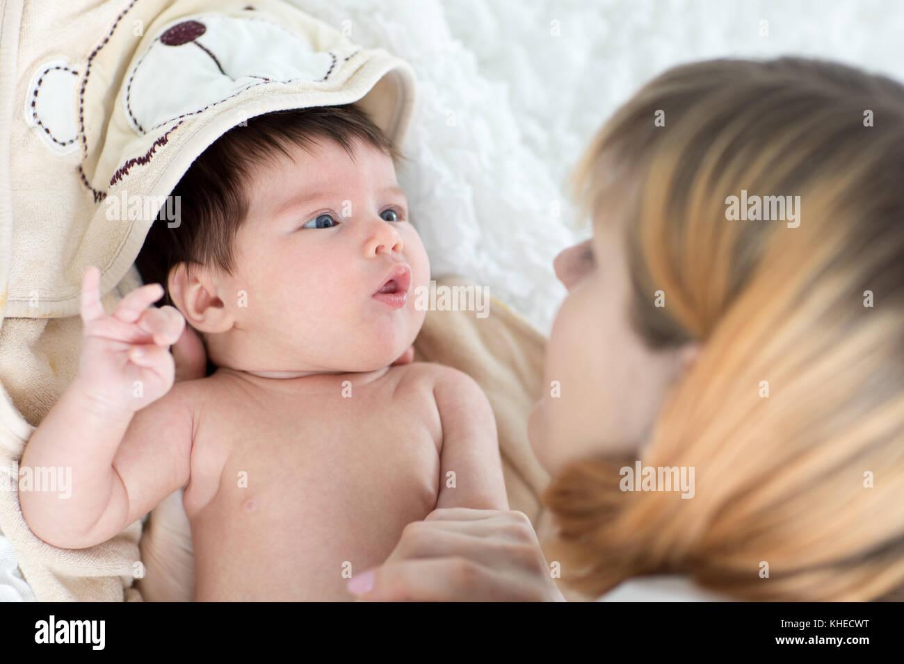 Glückliche Mutter und ihrem Baby Neugeborene jeweils andere suchen Stockbild