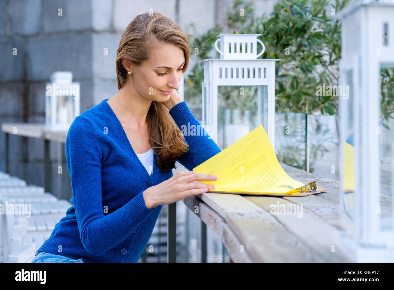 4d3fe6bf11837d Beautiful Woman Reading Menu Stockfotos & Beautiful Woman Reading ...