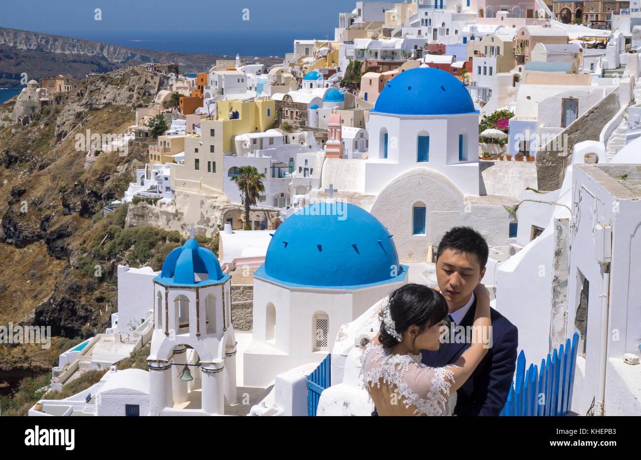 Brautpaar vor der orthodoxen Kirche im Dorf Oia, Santorin Insel, Kykladen, Ägäis, Griechenland Stockbild