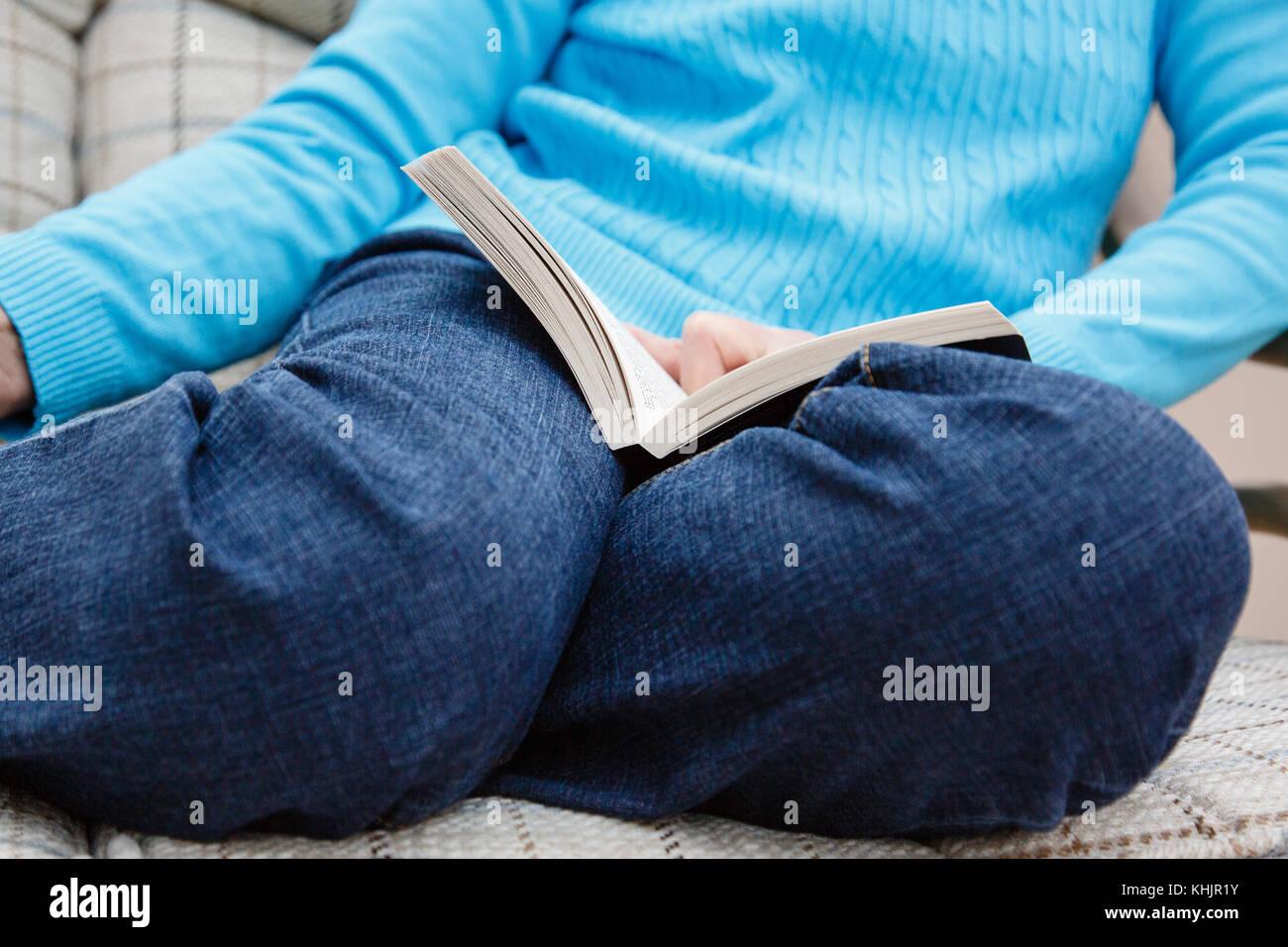 Eine ältere Frau Rentner trägt blaue Jeans sitzt auf einem Stuhl Lesung mit einem Buch auf den Knien in Stockbild