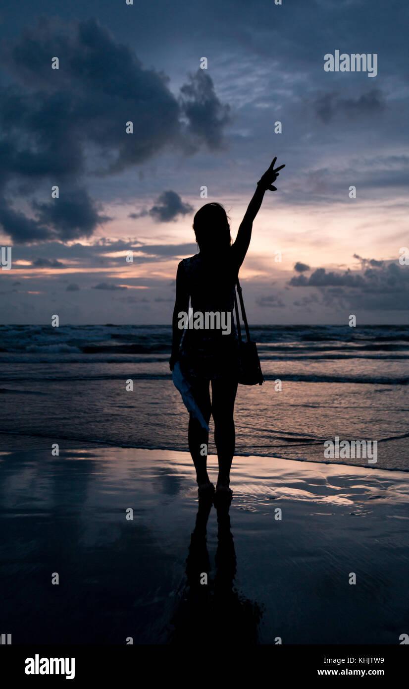 Frau dehnen ihre Hand in den Himmel, den schönen Sonnenuntergang Stockfoto