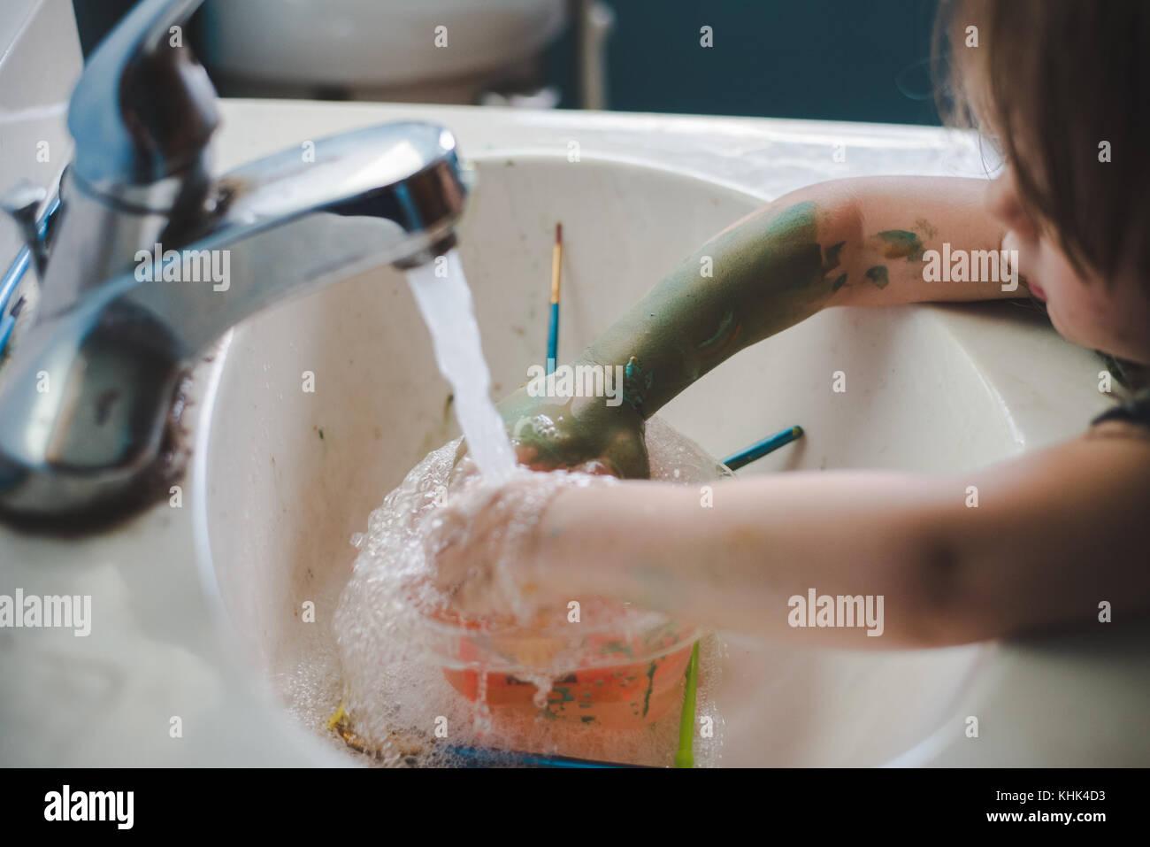 Ein Kleinkind Mädchen waschen Farbe weg die Hände in einem Waschbecken im Bad. Stockfoto