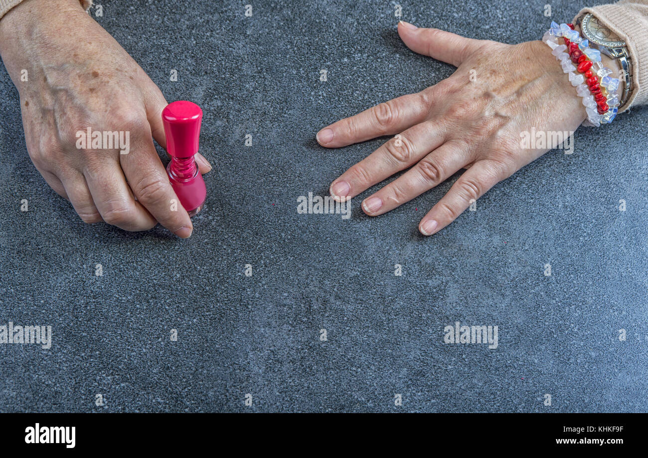 Maniküre. alte Frau Hände Polieren der Nägel mit rotem Nagellack in ...