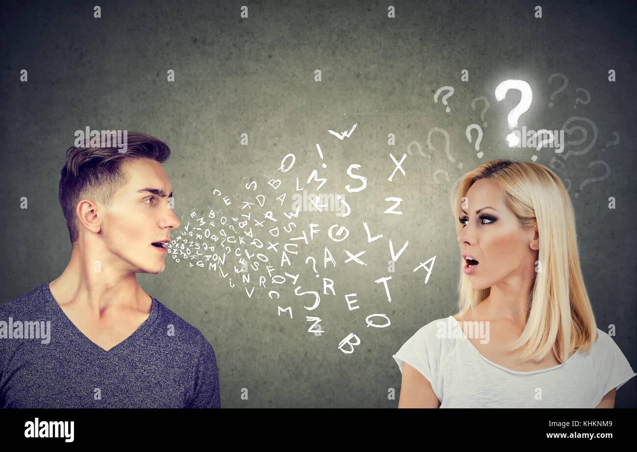 Sprachbarriere Konzept. schöner Mann sprechen, um eine attraktive junge Frau mit Fragezeichen Stockbild