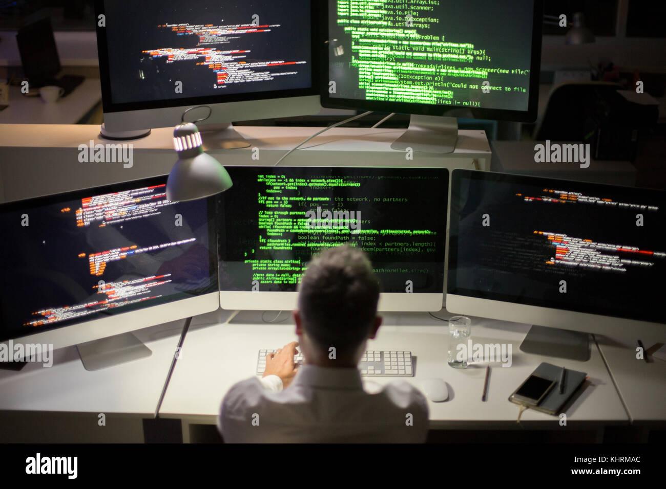https://c8.alamy.com/compde/khrmac/nicht-erkennbare-grauhaarige-software-entwickler-schreiben-code-wahrend-sitzen-vor-der-modernen-computer-interieur-der-dim-buro-im-hintergrund-khrmac.jpg