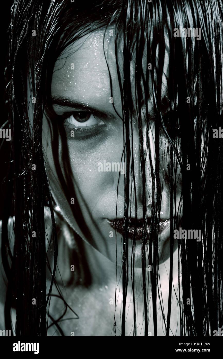 Ernsthafte wütende Frau mit nassen schwarzen Haar an Kamera Stockbild