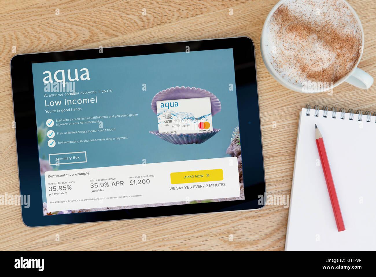 Die Aqua-Website bietet auf einem iPad Tablet Gerät, das auf einem Tisch liegt neben einem Notizblock und Bleistift Stockbild