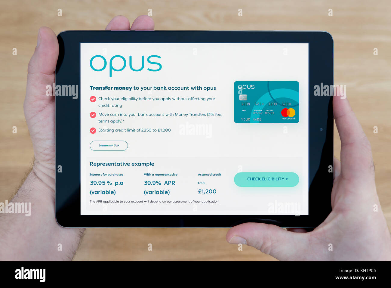 Ein Mann sieht im Opus Karte Website auf seinem iPad tablet device, Schuß gegen einen hölzernen Tisch Stockbild