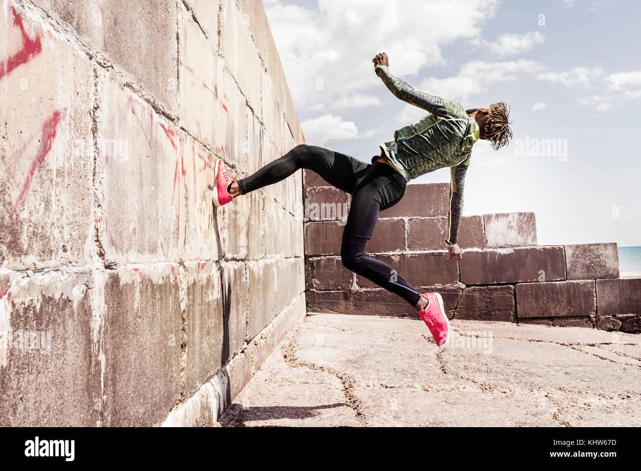 Junger Mann, Free Running, Outdoor, auf Seite der Wand Stockbild
