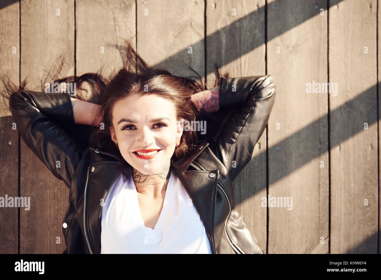 Porträt der jungen Frau liegend auf Holzterrasse, die Hände hinter dem Kopf, Lächeln, Ansicht von Stockbild