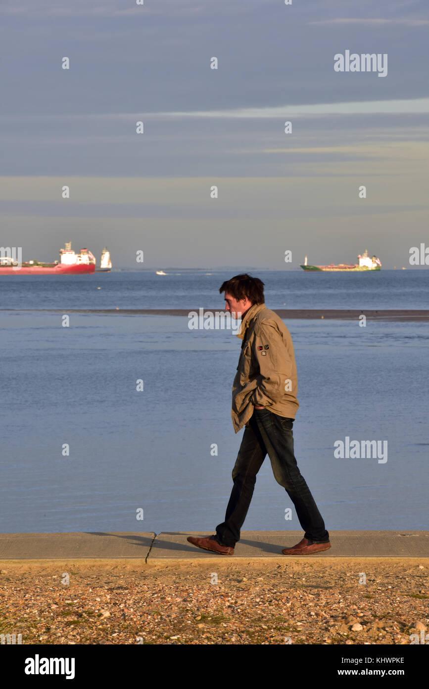 Ein Mann auf einem Meer an der Küste von bembridge auf der Insel Wight. Mann allein zu Fuß auf den Strand Stockbild