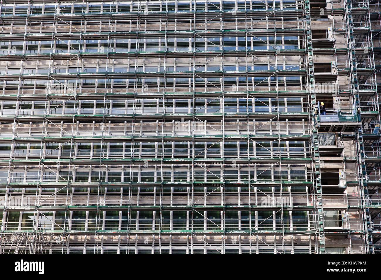 Deutschland, Köln, ein eingerüstet Bürogebäude an der Venloer Straße, ein einsamer Arbeiter. Stockbild