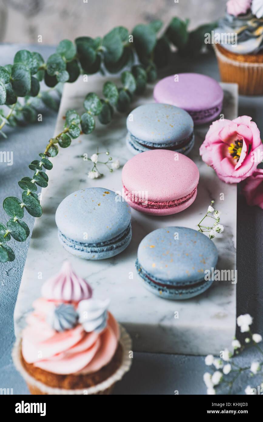 Pastellfarben Macarons, kleine Kuchen und Blumen auf Marmor Hintergrund. Hochzeit Süßigkeiten, Hochzeit Stockbild