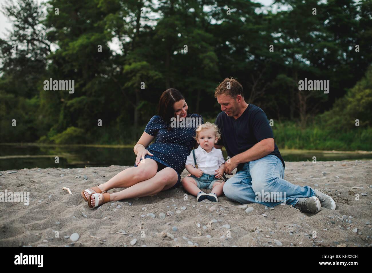 Schwangeren Paare sitzen am Strand mit männlichen Toddlersohn, Lake Ontario, Kanada Stockbild