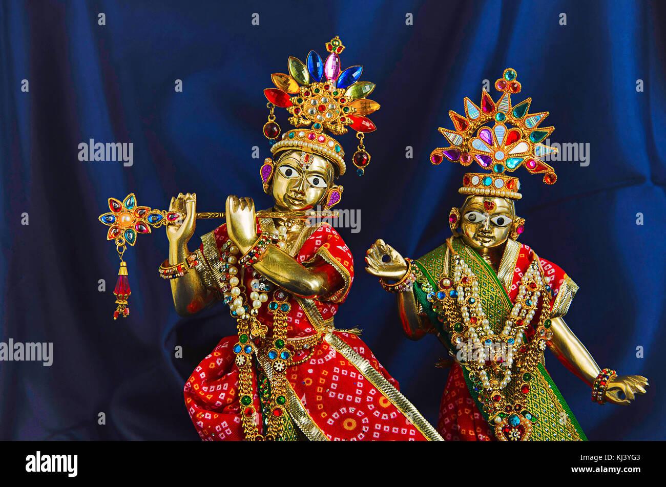 Messing Statue von Lord Krishna mit Flöte und radha (Teilansicht) mit mukut oder Krone auf dunkelblauem Hintergrund Stockbild
