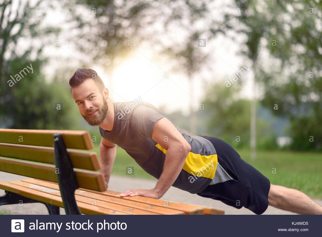 Junger Mann tun Push-ups in einem Park Stockbild