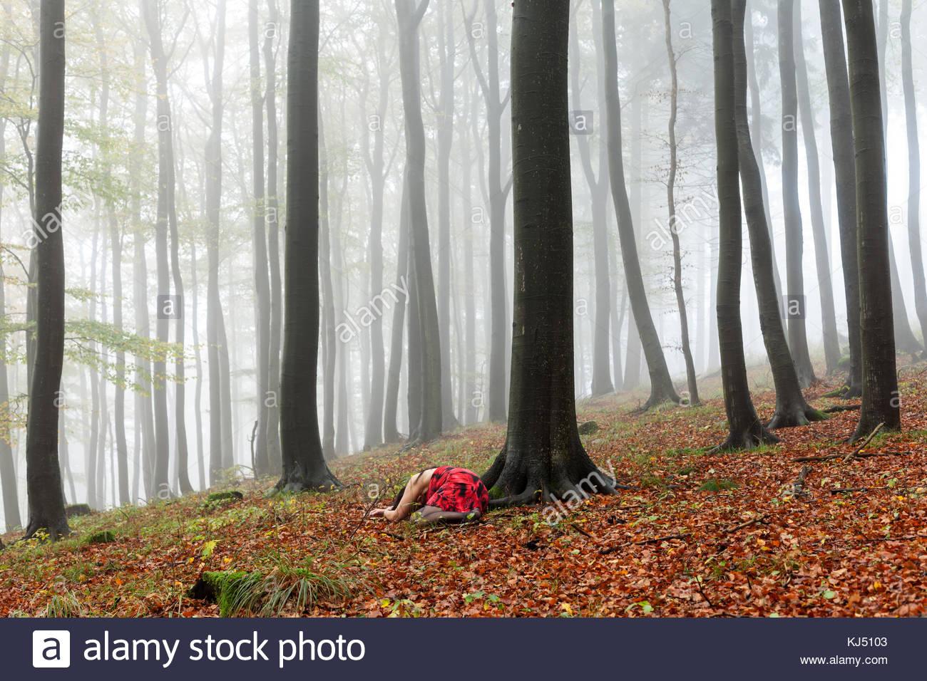 Misty Herbst Wald mit liegende Frau wie tot Stockbild