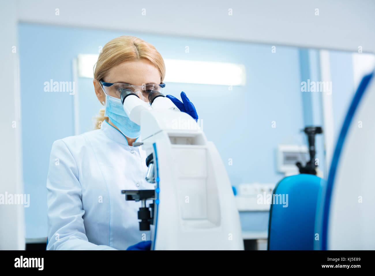 Viel versprechende Forscher im Mikroskop im Labor auf der Suche Stockbild
