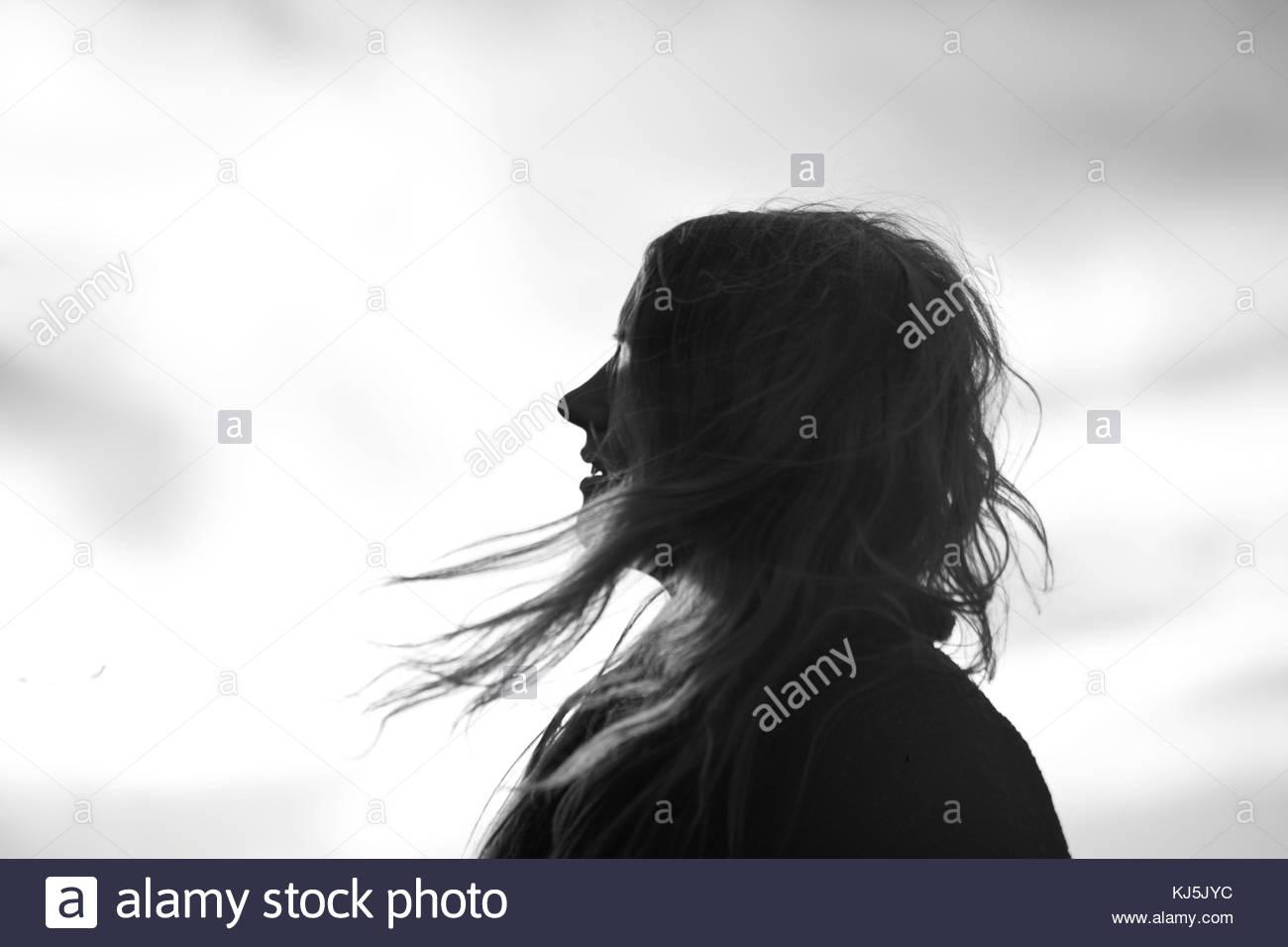 Silhouette der jungen Frau mit dem Wind im Haar Stockbild