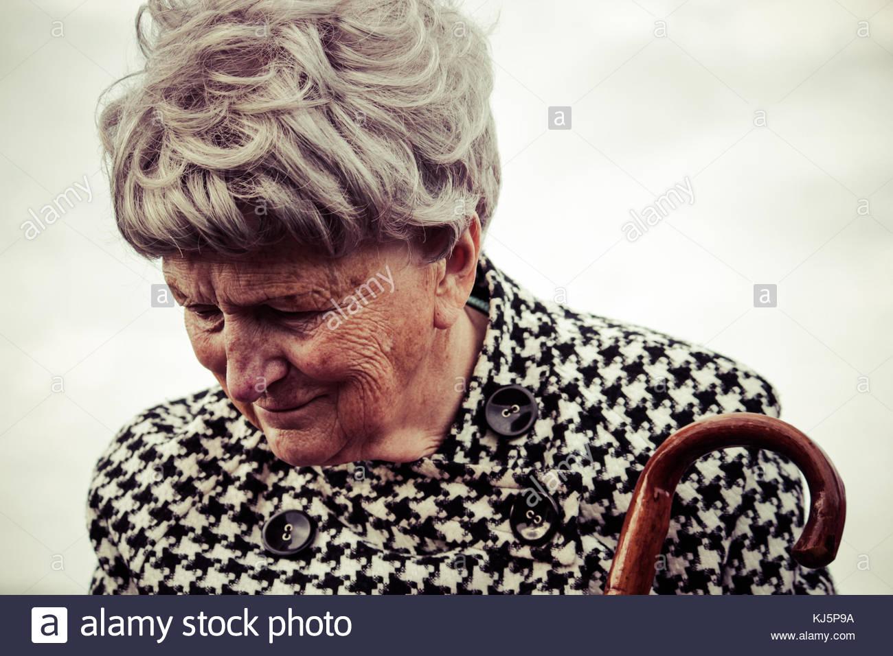 Ältere Frau in houndstooth Mantel, Regenschirm Stockbild
