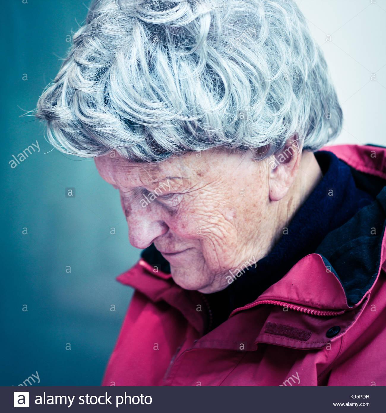 Ältere Frau im roten Mantel Stockbild