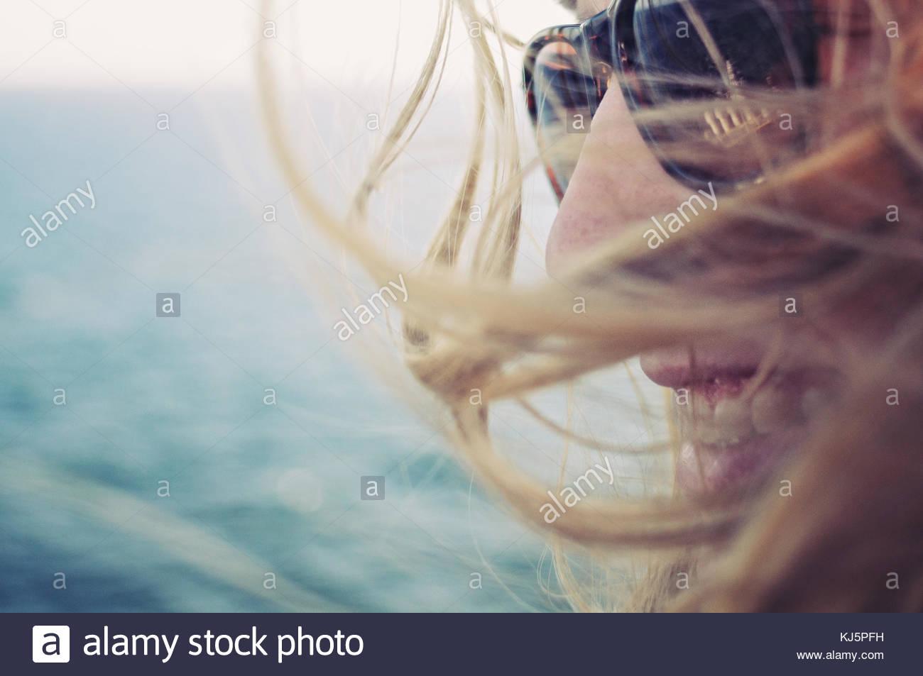 Lächelnde Frau mit langen Haaren und Sonnenbrille Stockbild