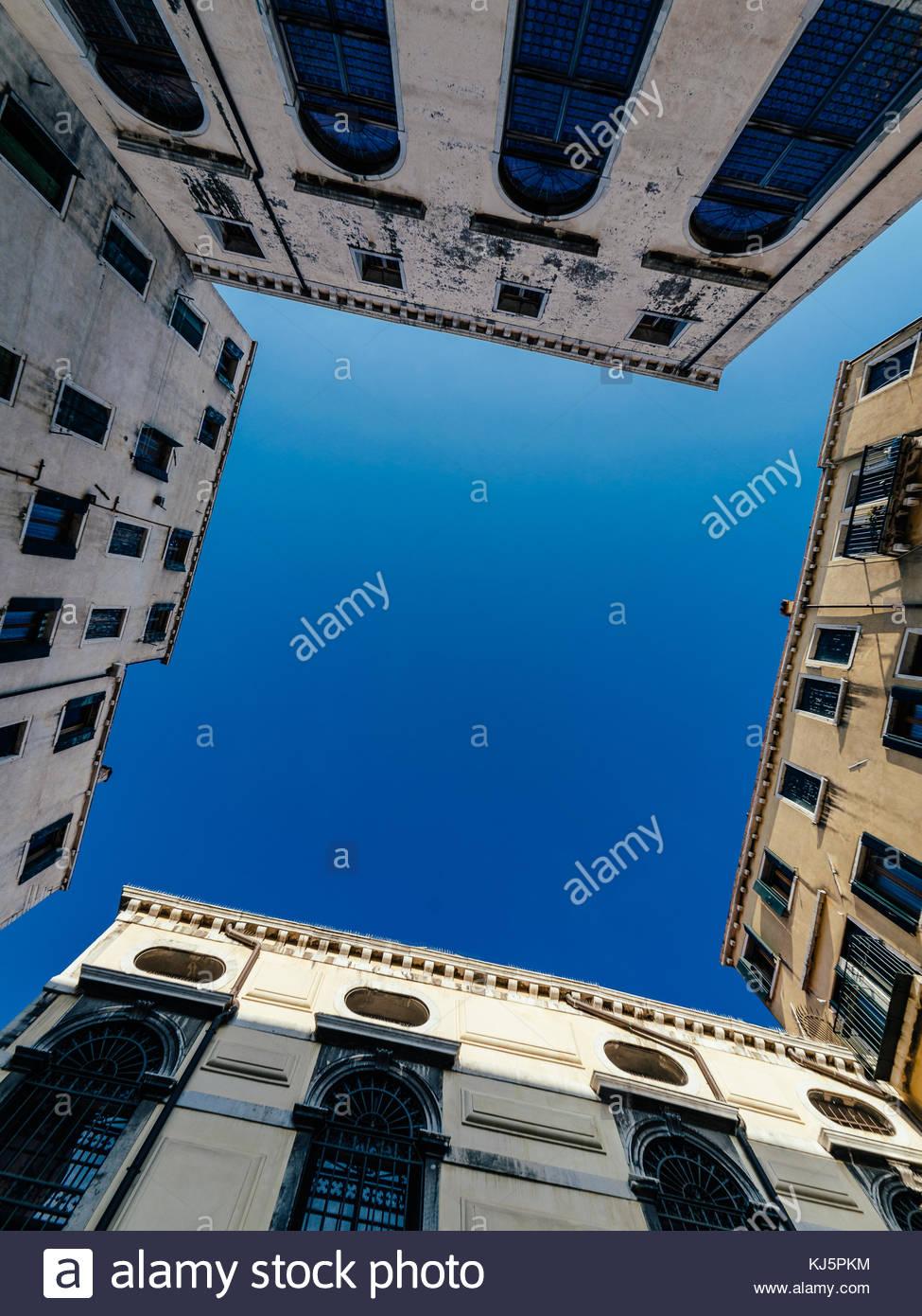 Blick in den Himmel von zwischen Gebäuden Stockbild