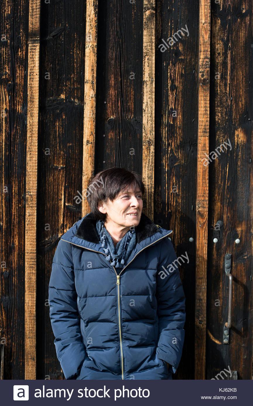 Reife Frau, die durch hölzerne Tür Stockbild