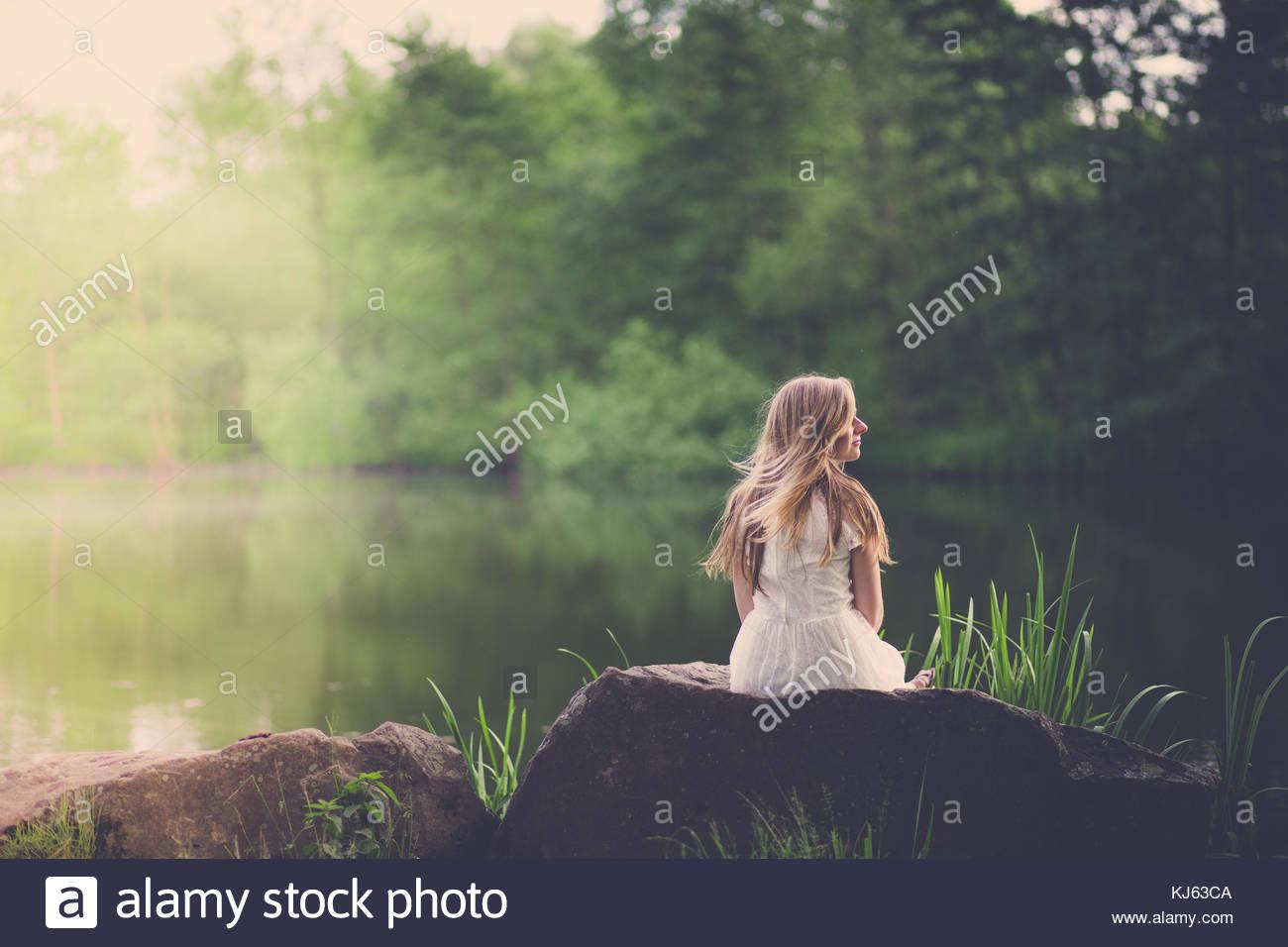 Blonde Frau entspannt in der Nähe von einem Teich Stockbild