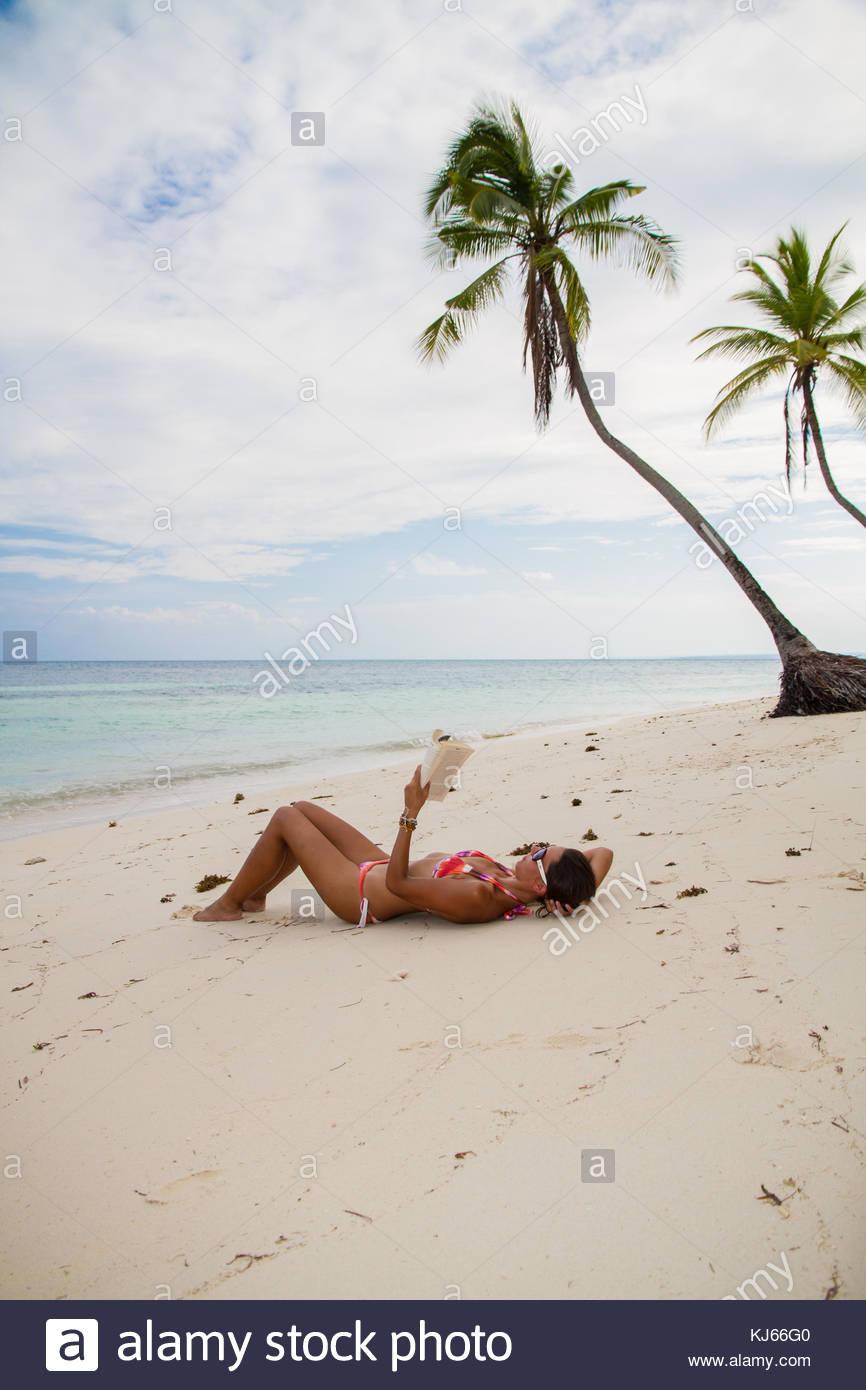 Junge Frau am Strand liegend mit Buch Stockbild