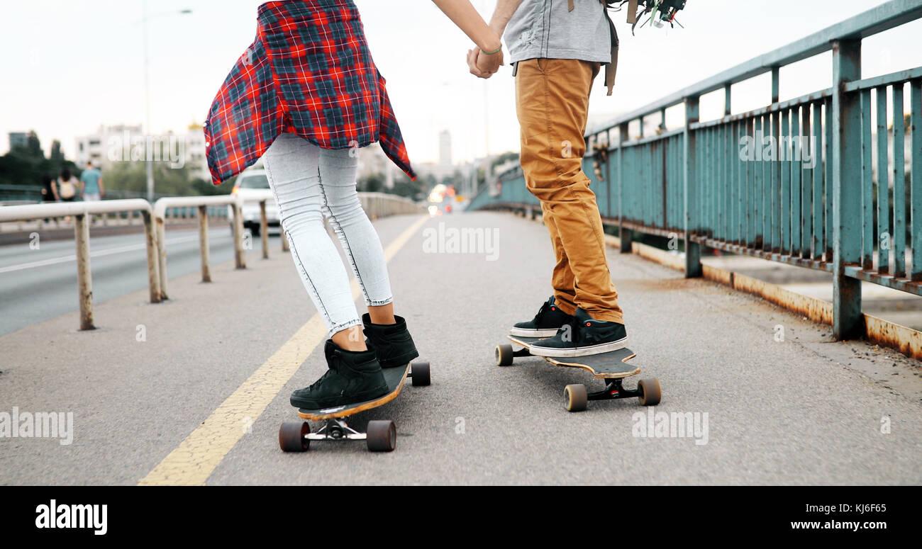 Junges attraktives Paar Skateboard fahren und Spaß haben Stockbild