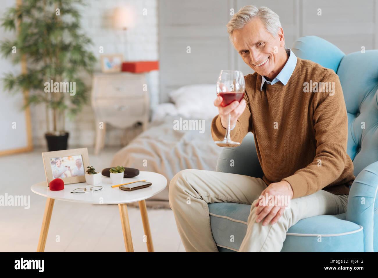 Freudige älterer Herr mit einem Glas Wein in die Kamera lächeln Stockbild