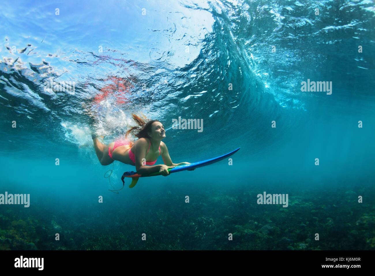 Aktive Mädchen im Bikini in Aktion. surfer Frau mit Surfbrett Tauchen Unterwasser unter brechen Big Wave. teenage Stockbild