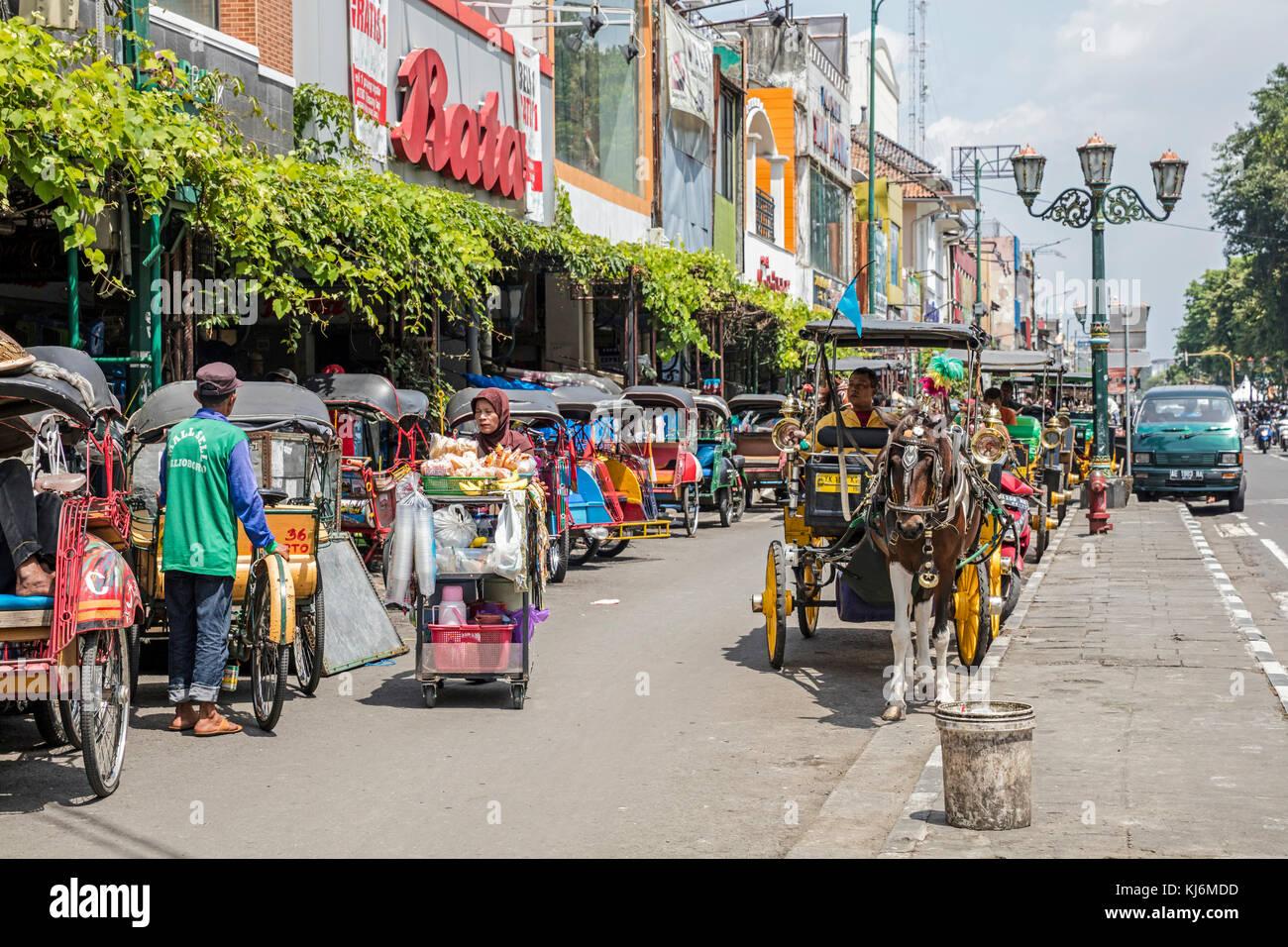 Zyklus Rikschas/becak und Pferdekutschen für den öffentlichen Verkehr in der Jalan Malioboro, wichtigsten Einkaufsstraße in Yogyakarta, Java, Indonesien Stockfoto